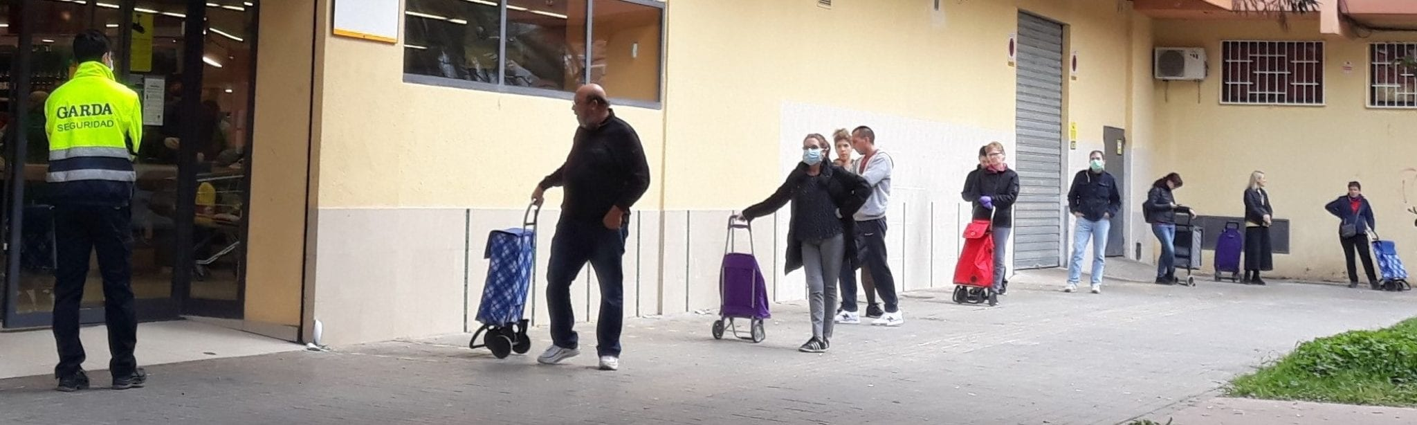 people practicing social distancing outside a clinic in Spain