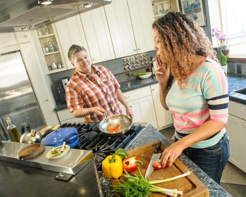 two women smoking weed and cooking healthy food - American Heart Association calls for deschechuling weed to improve research