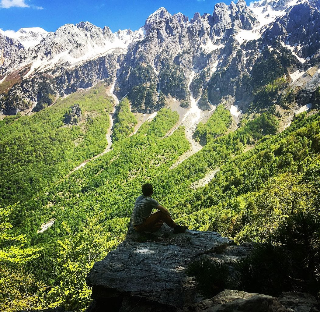 Nature amplifies therapeutic effects of psychedelics - study - person sitting rock mountains