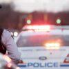 Mountie standing near flashing police cruiser