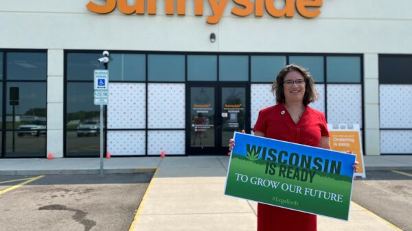 Sen. Melissa Agard standing outside an Illinois dispensary holding a sign saying, 'Wisconsin is ready'